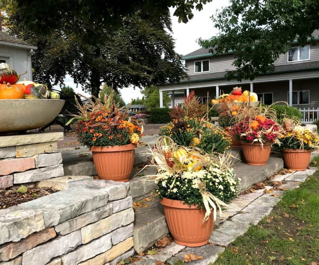 A variety of containers on stone steps filled with fall-themed decor and plants, designed by Bay Landscaping.